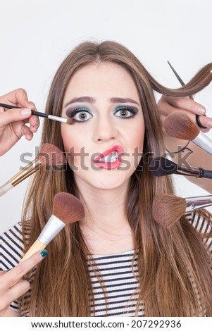 closeup of beautiful blond girl afraid of getting hair and makeup done isolated over white - stock photo