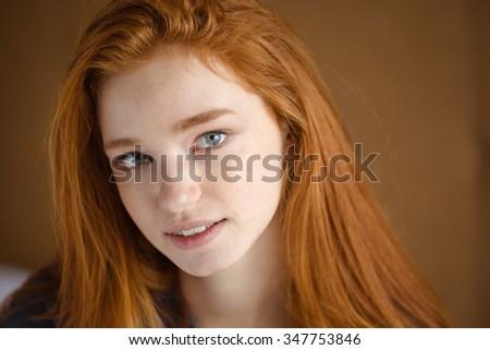 Closeup of beautiful cute natural girl with long red hair looking camera - stock photo