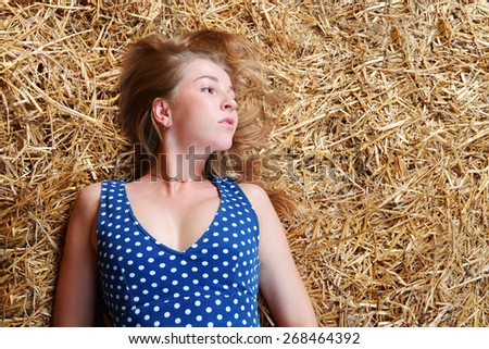 Closeup of beautiful girl with long blond hair lying on hay top view