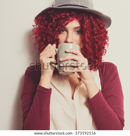 Closeup of beautiful girl with red curly hair in gray floppy hat, beige shirt and red cardigan drinking coffee or tea from gray mug. Modern young woman drinking hot beverage. Square format, filter. - stock photo