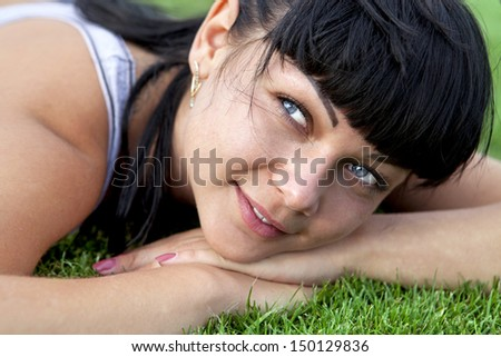 closeup of beautiful happy woman face that lies on grass
