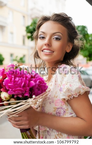 Closeup of beautiful pretty woman with bouquet of flowers. Outdoors - stock photo
