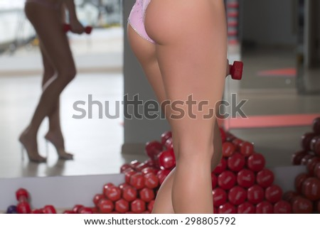 Closeup of beautiful sexual female bum with straight legs and hips in pink glamour panties standing in sport fitness hall near heap of red dumbells on mirror reflection background, horizontal picture - stock photo