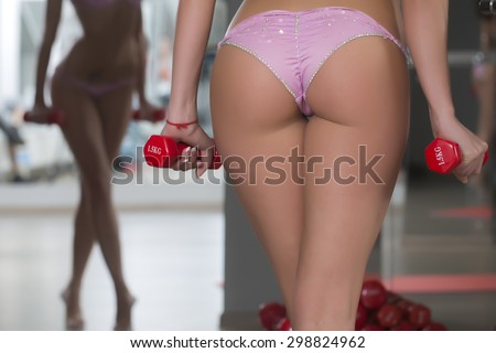Closeup of beautiful sexy beefy female bum with straight legs in pink glamour bikini standing in sport fitness hall holding red dumbells on mirror reflection background, horizontal picture - stock photo