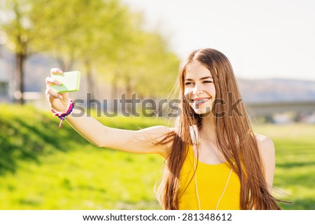 Closeup of beautiful teenage girl in yellow tank top taking a selfie on smart phone outdoors in summer. Young woman photographing herself smiling. Mild retouch, vibrant, natural light, horizontal. - stock photo