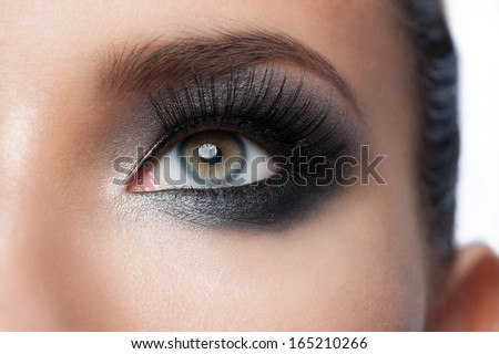 Closeup of beautiful woman eye with bright stylish makeup with long lashes - stock photo