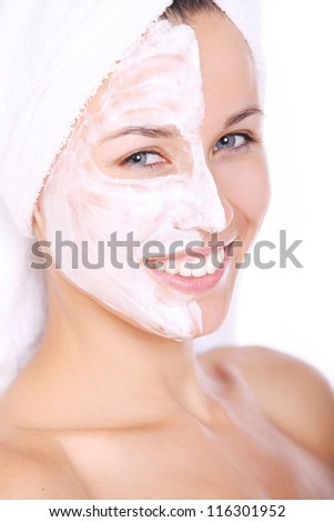 Closeup of Beautiful woman in towel with facial mask over white background