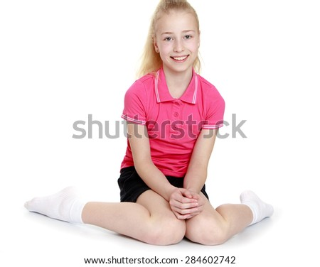Closeup of beautiful young blonde girl is sitting on the floor- isolated on white background - stock photo