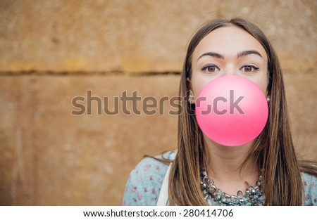 Closeup of beautiful young brunette teenage girl blowing pink bubble gum over a stone wall background - stock photo