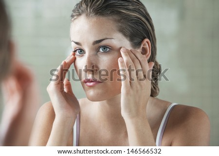 Closeup of beautiful young woman examining herself in front of mirror - stock photo