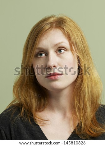 Closeup of beautiful young woman looking away on colored background