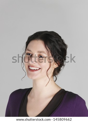 Closeup of beautiful young woman smiling on grey background