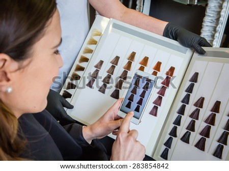 Closeup of beautiful young woman taking a photo with her smartphone to the hair dye palette - stock photo