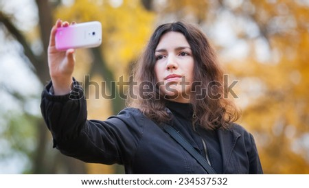 Closeup of beautiful young woman taking a selfie photo with smart phone outdoors on sunny summer day - stock photo