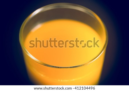 Closeup of beautifully colored orange juice in a transparent glass shot from above side angle - stock photo