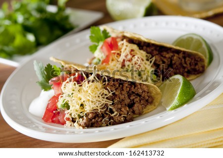 Closeup of beef tacos with tomatoes, guacamole and sour cream. - stock photo