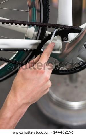 Closeup of bicycle mechanic repairing a bike in workshop - stock photo