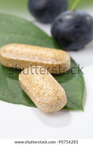 Closeup of bilberry extract pills and fresh berries and leaves best suited for alternative medicine ads - stock photo