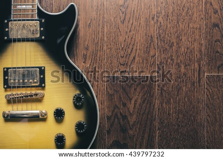 Closeup of black and yellow electric guitar on wooden brown surface - stock photo