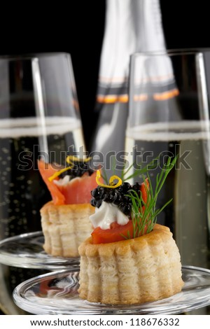 Closeup of black caviar on Creme Fraiche and smoked salmon canape and flutes of Champagne over black background. - stock photo