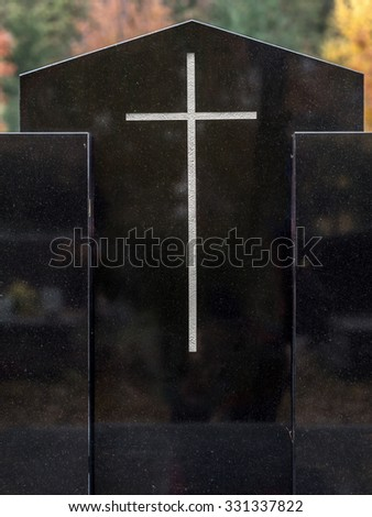 Closeup of black granite tombstone with white cross