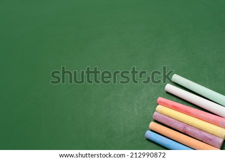 Closeup of blank green blackboard with pieces of coloured chalks. - stock photo