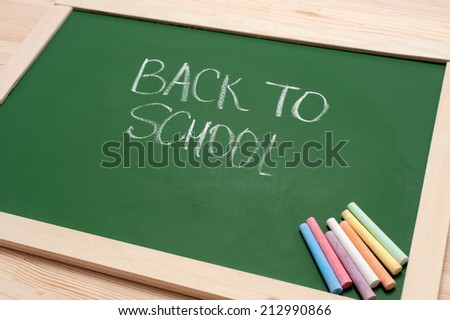Closeup of blank green blackboard with pieces of coloured chalks and 'back to school' text on wooden surface. Angle view. - stock photo