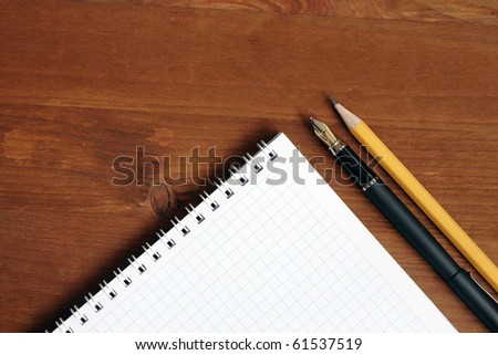 Closeup of blank spiral notebook near pen and pencil on wooden table