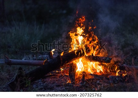 Closeup of blazing campfire coals in the night - stock photo