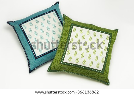 Closeup of blue and green printed cushions on white background - stock photo