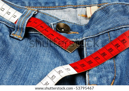 Closeup of blue jeans and measure tape - stock photo