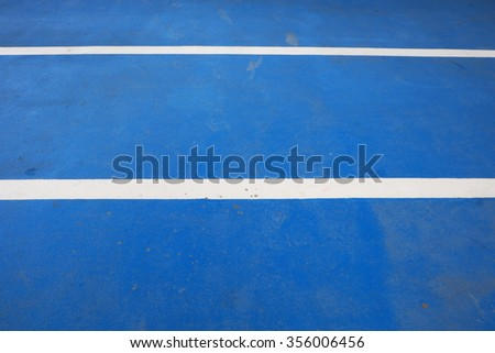Closeup of blue running race track with two white rubber lines. - stock photo