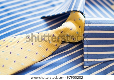 closeup of blue shirt with stripes and yellow tie - stock photo