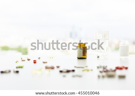Closeup of blurry white table with colorful pills and capsules, medicine bottles and a glass of water. Selective focus - stock photo