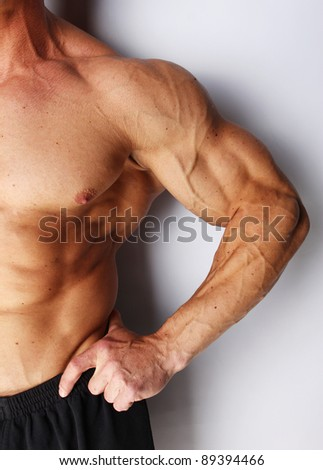 Closeup of body builders arm, isolated on grey - stock photo