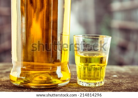 Closeup of Bottle and glass shot with yellow liqour resembling whiskey, rum, tequila, spirit on wooden table - stock photo