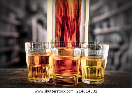 Closeup of Bottle and glass shots with yellow liqour resembling whiskey, rum, tequila, spirit on wooden table - stock photo