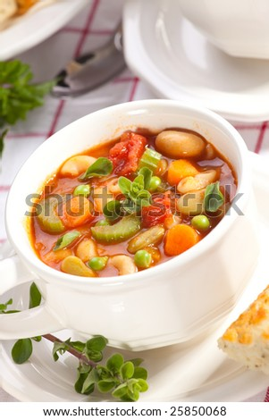 Closeup of bowl of hot fresh Minestrone soup and cheese garlic bread sticks - stock photo