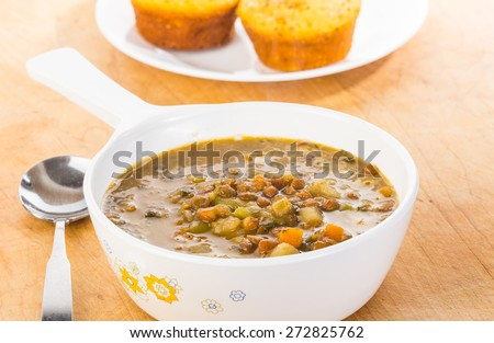 Closeup of bowl of organic lentil and vegetable soup on wooden background with cornbread muffins. - stock photo