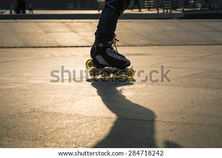 Closeup of boy playing roller blade in park with sunset light - stock photo