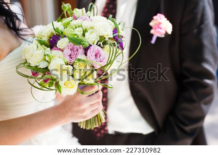 Closeup of bride and groom holding a wedding bouquet in the middle