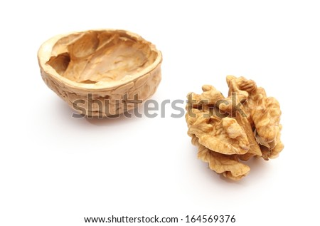 Closeup of brown walnut without shell and nutshell in background. Isolated on white background - stock photo