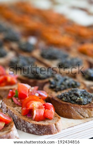 Closeup of bruschetta appetizers with savoury paste and tomato toppings presented in rows - stock photo