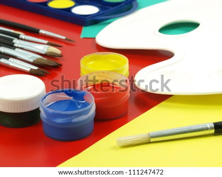 Closeup of brush and open jars of paint
