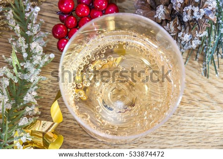 Closeup of bubbly drink from above on wood with berries, greenery, ribbon and a pinecone with ice crystals, winter decor