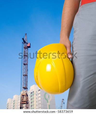 Closeup of builder with yellow helmet on building panorama background