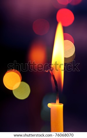 Closeup of burning candle front of multi-colored lights - stock photo