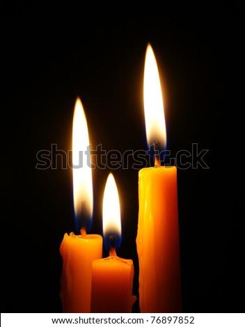 Closeup of burning candle isolated on black background - stock photo
