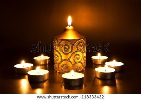 Closeup of burning candles on dark background - stock photo