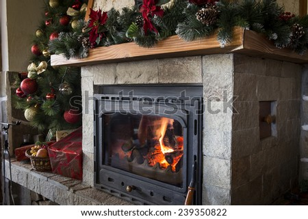 Closeup of burning fireplace and christmas decorations - stock photo